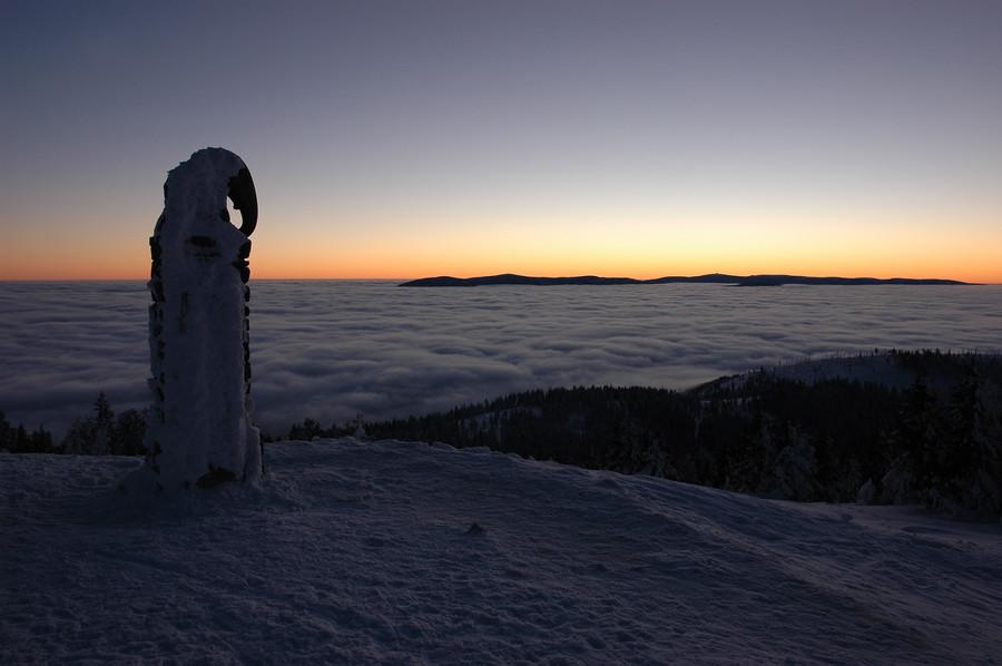 Ráno na Králickém Sněžníku. Z inverze na obzoru vystupuje hřeben Jeseníků s Pradědem (vysílač).