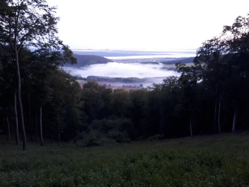 Před zárubami, svítá a v údolí se válí mlhy.